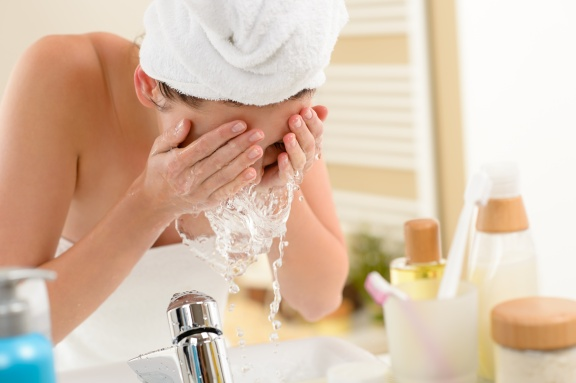 Woman splashing face with water in bathroom